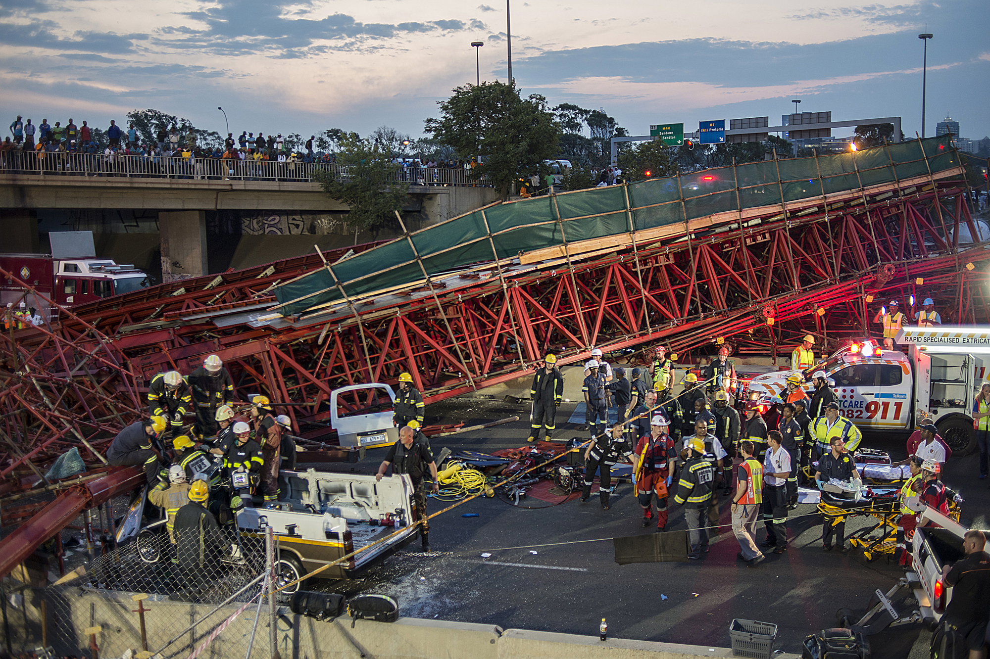 South African paramedics and first aid workers work on the rubble of a collapsed pedestrian bridge where at least two people were killed, on October 14, 2015 in Johannesburg. AFP PHOTO / MUJAHID SAFODIEN